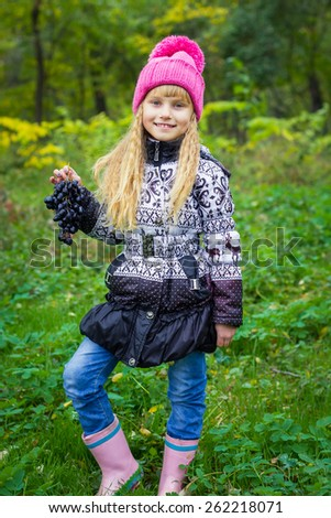 Adorable little blond girl with long blond hair in autumn park. Beautiful little young baby in a pink hat with grapes in their hands - stock photo