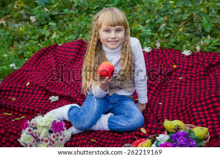 Adorable little blond girl with long blond hair in autumn park. Beautiful little young baby in a pink hat with an apple in his hand. Beautiful child sitting on a red plaid.  - stock photo