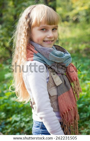 Adorable little blond girl with long blond hair in autumn park. Beautiful little young baby stands in a scarf.  Lovely child smiling