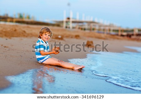 Adorable little blond kid boy having fun with building sand castle on the beach of ocean or see by sunset. Happy child spending active vacations. - stock photo
