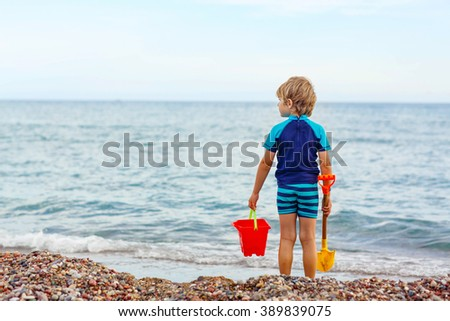 Adorable little blond kid boy standing on lonely ocean beach. Child playing with bucket and shovel and looking on horizon. Vacations, summer, travel concept. Preschooler enjoying summer vacations  - stock photo
