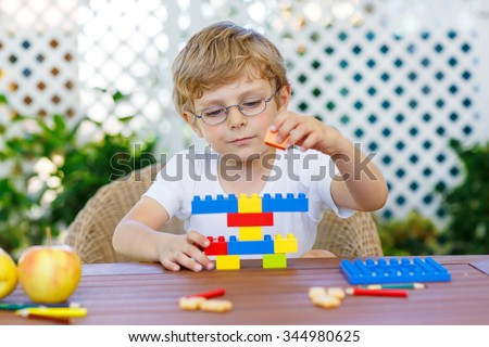 Adorable little blond kid with glasses playing with lots of colorful plastic blocks indoor. Active child having fun with building and creating. Creative Leisure for children. - stock photo