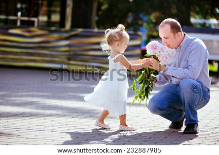 Adorable little blonde girl gives daddy peonies - stock photo