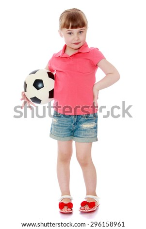Adorable little blonde girl in denim shorts and red shirt is holding under his arm a soccer ball - isolated on white background - stock photo