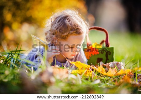 Adorable little blonde girl lies in yellow leafs - stock photo