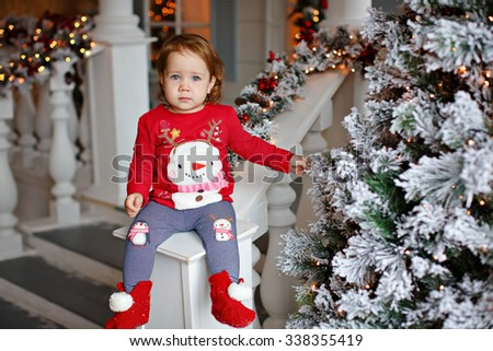 Adorable little blonde girl little girl in a sweater with a snowman sitting on the stair railing Christmas decorations and a little sad - stock photo