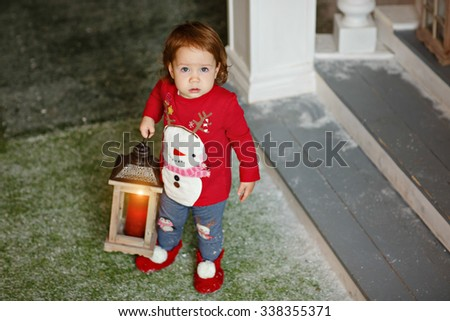 Adorable little blonde girl little girl in a sweater with a snowman stands in the Christmas decorations and holds a lantern in his hand