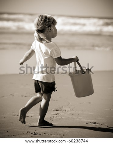 Adorable little blonde girl with ehr bucket at the beach