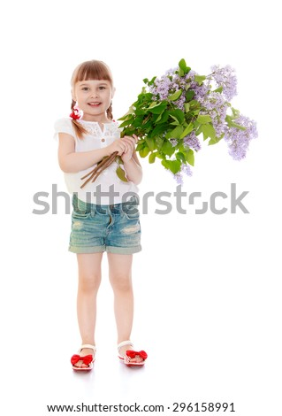 Adorable little blonde girl with short bangs and braided pigtails , a white t-shirt and short denim shorts hugs bouquet of lilacs - isolated on white background - stock photo