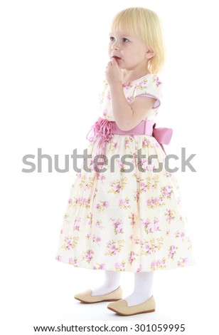 Adorable little blonde girl with short hair in a long flowered dress tied with a pink belt. Girl with surprise looks aside, probably about something thinks-Isolated on white background - stock photo