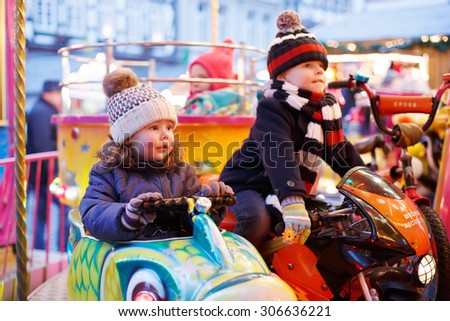 Adorable little boy and girl, siblings on a carousel at Christmas funfair or market, outdoors. Happy children, friends having fun. Selective focus on one child. Holiday, children, lifestyle concept. - stock photo