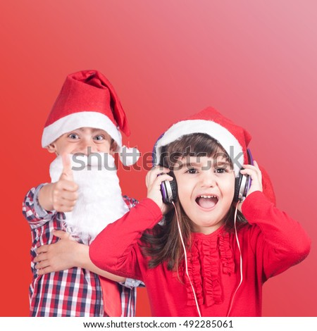 Adorable little boy and girl wearing a Santa hat listening to music and singing Christmas carols. (Selective focus image)