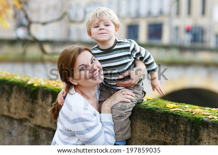 Adorable little boy and mother hugging in autumn city and looking at the camera - stock photo