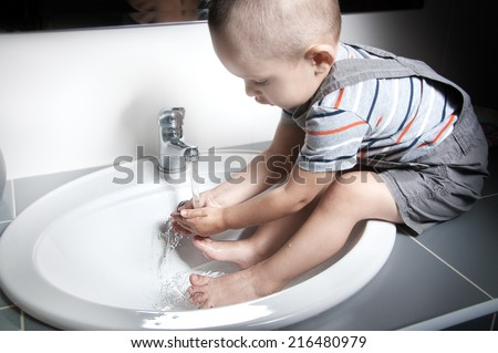 Adorable  little boy at the age of two in a striped T-shirt  looking at the flow of water in the sink and washing her hands and feet in the sink - stock photo