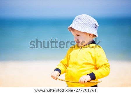 Adorable little boy at the beach playing with sand - stock photo