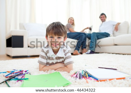 Adorable little boy drawing lying on the floor in the living room