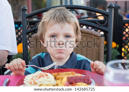 Adorable little boy eating french fries in summer, outdoors - stock photo