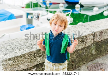 Adorable little boy eating ice cream on a nice summer day - stock photo