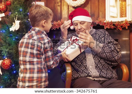 adorable little boy gives a christmas gift to his grandfather - stock photo