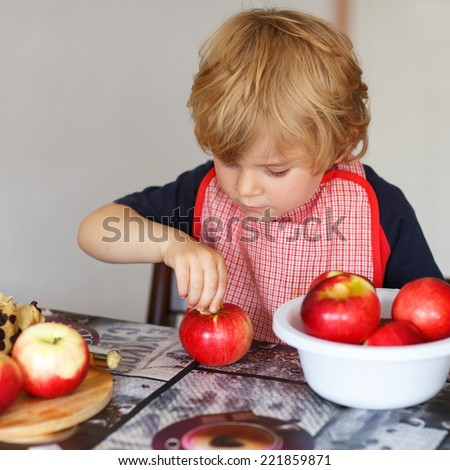 Adorable little boy helping and baking apple pie in home''s kitchen, indoor. Filling apple with marzipan - stock photo