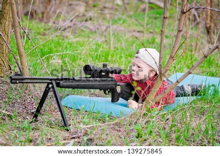 Adorable little boy holding a toy rifle and ready to shoot