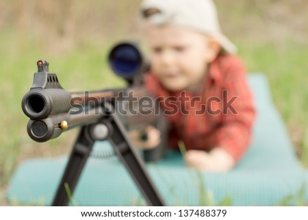 Adorable little boy holding a toy shotgun and ready to shoot - stock photo
