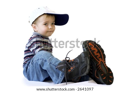 Adorable little boy in a very big shoes - stock photo