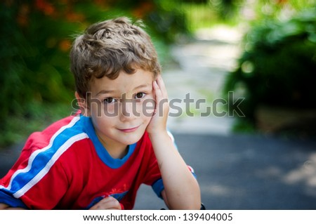 adorable little boy looking at the camera with a shy smile and big brown eyes - stock photo