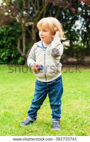 Adorable little boy of 3-4 years old playing in park, wearing grey jacket and denim jeans - stock photo