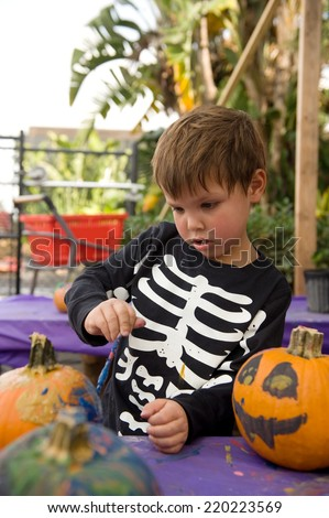 Adorable little boy painting a pumpkin for Halloween  - stock photo