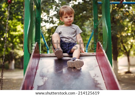 Adorable little boy playing on a slide in a kids outdoor playground sitting at the top with a quaint expression as he prepares to slide down - stock photo