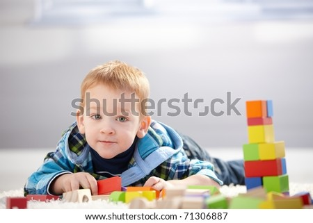Adorable little boy playing with building cubes at home, laying on floor.? - stock photo