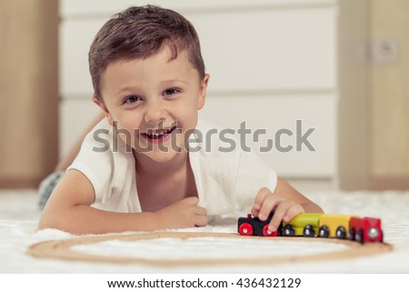 Adorable little boy playing with toys lying on the floor at the day time. Concept of happy childhood. - stock photo