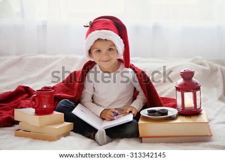 Adorable little boy, preparing for Christmas holidays, writing to Santa - stock photo