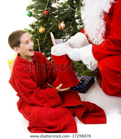 Adorable little boy receives a Christmas stocking from Santa Claus.