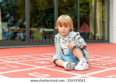 Adorable little boy resting on a schoolyard, toned image - stock photo