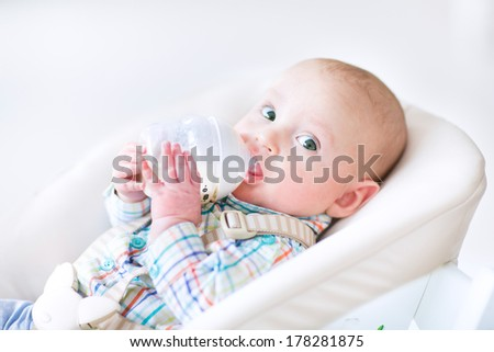 Adorable little boy sitting in a high chair drinking milk from a plastic bottle - stock photo