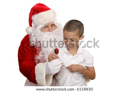 Adorable little boy sitting on Santa's lap and getting a lolipop.  Isolated on white.