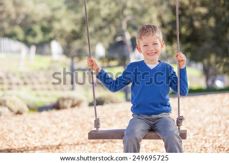 adorable little boy swinging in the park  - stock photo