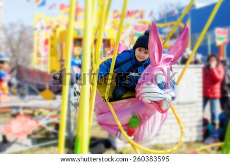 Adorable little boy, swinging on a pink rabbit in amusement park - stock photo