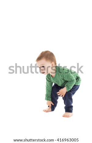 Adorable little boy trying to stand up isolated over white background - stock photo