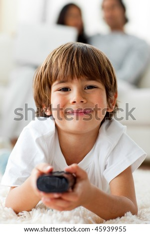 Adorable little boy watching TV lying on the floor in the living-room - stock photo