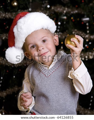 Adorable little boy wearing a Santa Hat in front of a Christmas tree - stock photo