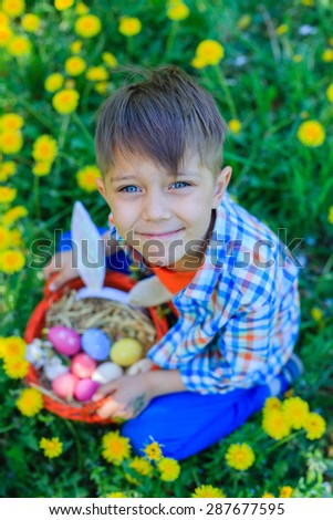 Adorable little boy wearing bunny ears playing with Easter eggs in blossoming dandelion on spring day - stock photo