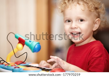 Adorable little boy with a mischievous smile and curly blond hair playing with a colourful plastic toy microphone - stock photo