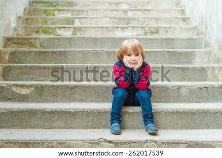 Adorable little boy with blond hair sitting on steps in a city on a nice sunny day, wearing warm pullover, jeans and blue moccasins - stock photo