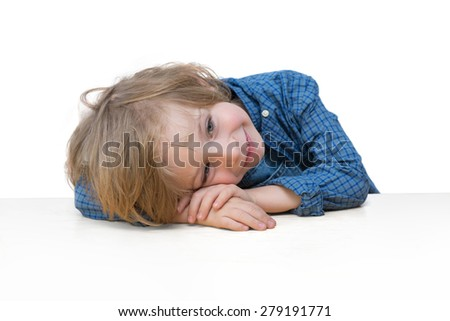 Adorable little boy with blonde hair, blue eyes, smiling on the white table edge isolated over white background  - stock photo