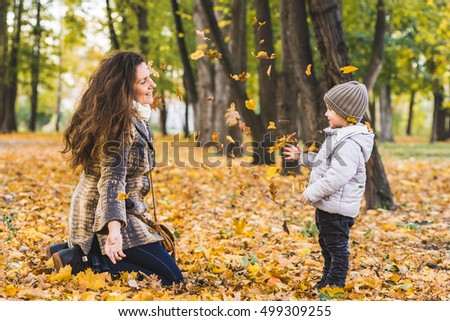 Adorable little boy with his mother in autumn park. Mother and son throws yellow leaves