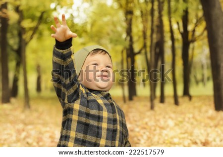 Adorable little boy with outstretched hand in autumn park - stock photo