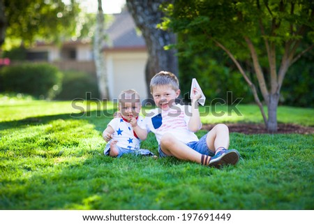 Adorable little brothers flying paper airplanes  - stock photo